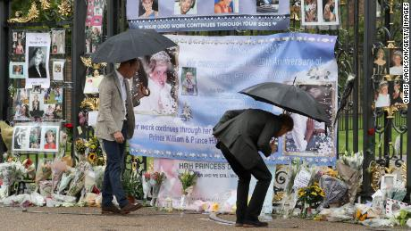 The brothers look upon flowers, photos and other souvenirs left as a tribute to Princess Diana near the Sunken Garden at Kensington Palace in London on August 30, 2017.