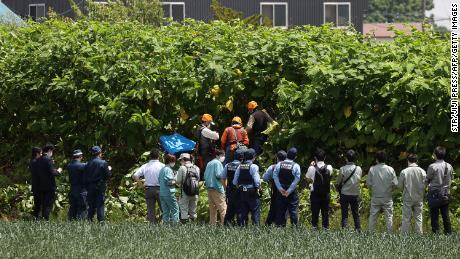 Police officers and members of a hunting group search for a brown bear in Sapporo, Japan, on June 18.