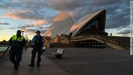 Police officers walk past the Sydney Opera House during the first day of lockdown on Saturday.
