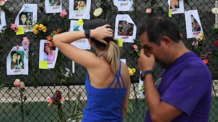 Passersbylook at photos of missing people posted to a fence on June 26, 2021, in Surfside, Florida.