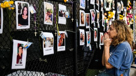 A woman prays in front of photos at the makeshift memorial for the victims of the building collapse, near the site of the accident in Surfside, Florida on June 27, 2021.