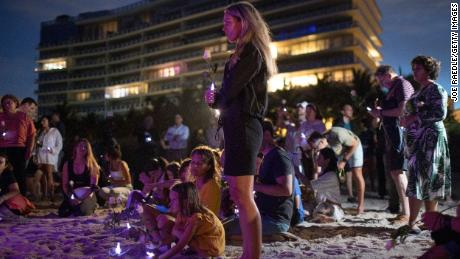 People join together in a community twilight vigil on the beach for those lost and missing during the partially collapsed Champlain Towers South condo building on June 28, 2021 in Surfside, Florida.