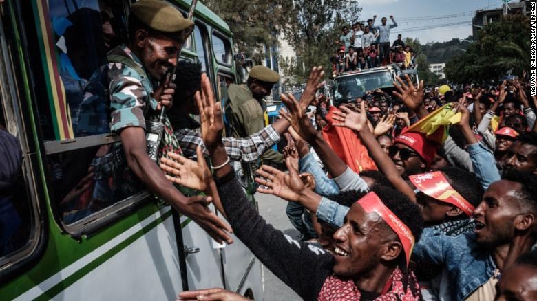 People try to shake hands with soldiers of Tigray Defence Force (TDF) as they arrive in Mekelle, the capital of Tigray region, Ethiopia, on June 29.