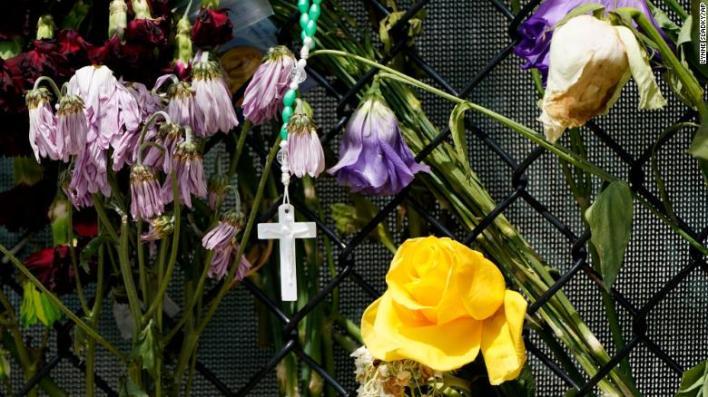 Una cruz cuelga entre flores marchitas en un memorial improvisado cerca de Champlain Towers South.