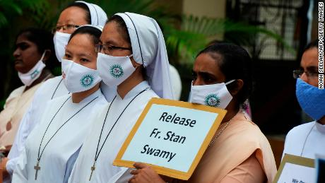 Catholic nuns hold placards to protest the arrest of Jesuit priest Father Stan Swamy on October 21, 2020.