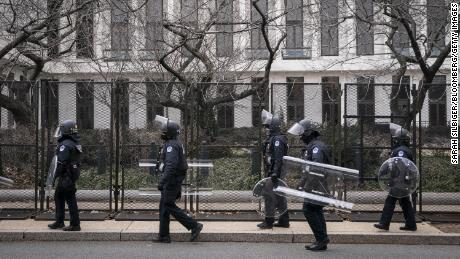 US Capitol police officers in protective riot gear walk by the fenced perimeter of the U.S. Capitol grounds in Washington, D.C., on Friday, January 29, 2021.