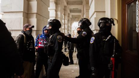 Capitol Police in riot gear face off against a group of pro-Trump protesters after removing them from the Capitol Building on January 6, 2021 in Washington, DC.