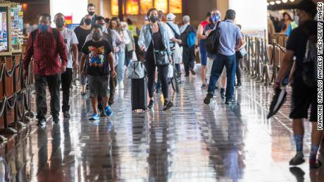 People wearing face masks walk through Union Station in Los Angeles on June 29, 2021.  California is one of 24 states that are seeing a rise in cases of Kovid-19.