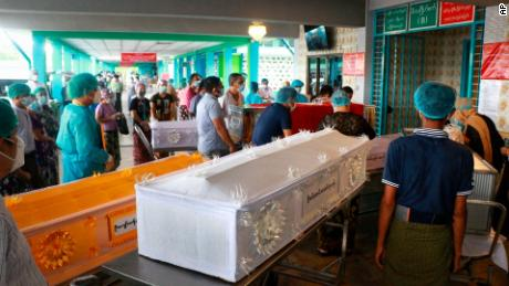 People wearing face masks wait while caskets with bodies are queued outside a crematorium at the Yay Way cemetery in Yangon, Myanmar, on July 14.