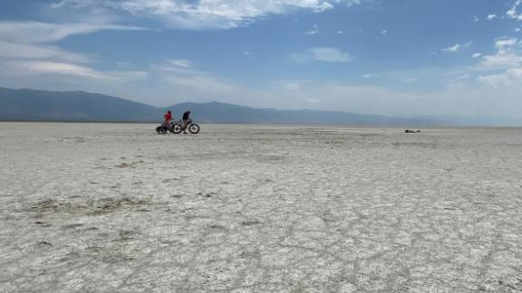 Lucy Kafanov of CNN and Kevin Perry ride bikes Tuesday on the dry lake bed playa of the Great Salt Lake.