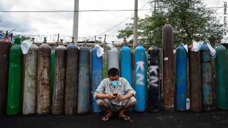 A man uses his mobile phone in front of empty oxygen canisters outside a factory in Mandalay on July 13.