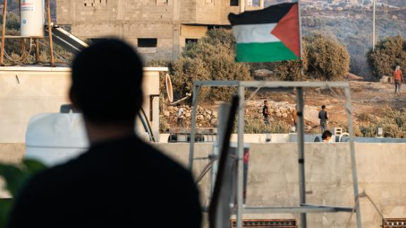 The Palestinian flag flies above the scene of clashes between Palestinians and Israeli soldiers in Beita.