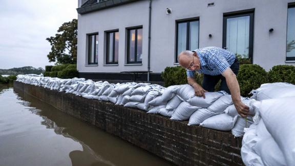 A resident of Arcen, Netherlands, looks at the rising water of the Meuse River on Saturday.