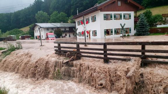 Water flows over a square in front of a house in Bischofswiesen, Germany.
