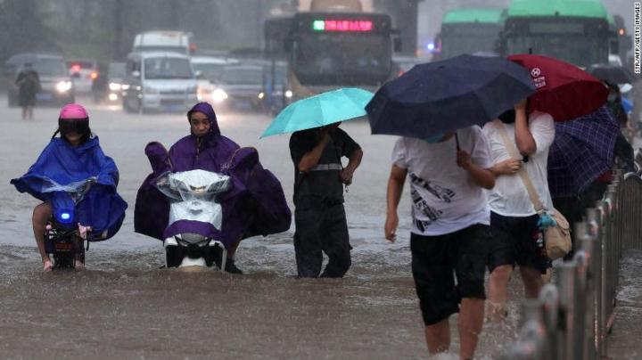 People wading through flood waters in Zhengzhou, Henan, China, on July 20.