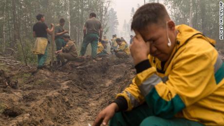 Mitarbeiter des Waldschutzdienstes Yakutlesresurs ruhen sich aus, während sie einen Feuerschneisengraben ausheben, um ein Feuer außerhalb des Dorfes Magaras in Jakutien zu stoppen.
