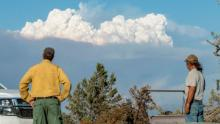 Fire Mitigation and Education Specialist Ryan Berlin (L) and Bob Dillon watch the Bootleg Fire smoke cloud from Dillon's home in Beatty, Oregon, on July 16, 2021.