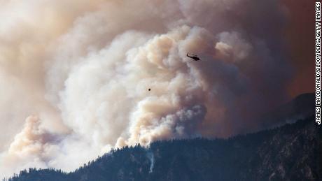 Ein Hubschrauber bereitet sich darauf vor, am Freitag, den 2. Juli 2021, einen Wassertropfen zu machen, während Rauch entlang des Fraser River Valley in der Nähe von Lytton, British Columbia, Kanada, aufsteigt.