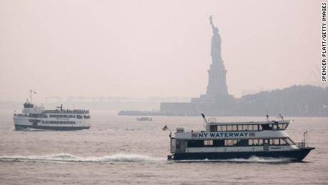 The Statue of Liberty sits behind a cloud of haze on July 20, 2021, in New York City. According the National Oceanic and Atmospheric Administration, wildfire smoke from wildfires has arrived in the tri-state area creating decreased visibility and a yellowish haze in many areas.