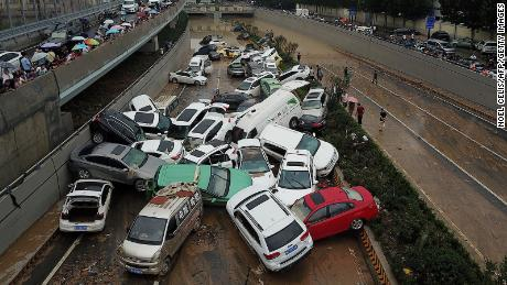 Cars sit in flood water at the entrance of a tunnel after heavy rain in Zhengzhou city on July 22, 2021.