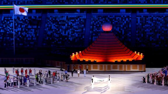 The Olympic flag is carried toward the Olympic cauldron during the opening ceremony.