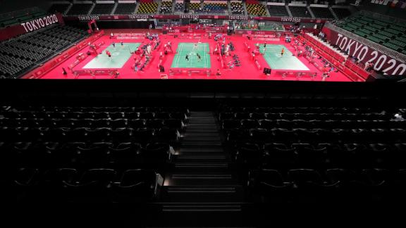 Badminton players compete amid rows of empty seats on July 24.