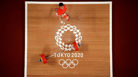Chinese weightlifter Chen Lijun celebrates on July 25. He won gold in his 67-kilogram weight class after lifting 187 kilograms — an Olympic record — in the clean-and-jerk. His total lift of 332 kilograms edged Colombia's Luis Javier Mosquera Lozano by one kilogram.