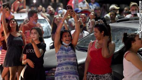 People celebrate in the street after Tunisian President Kais Saied announced the dissolution of parliament and Prime Minister Hichem Mechichi's government in Tunis on July 25, 2021.