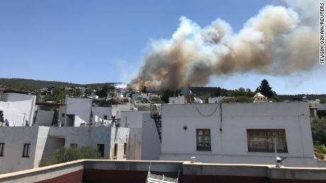 Plumes of smoke from a forest fire are seen near a residential area at a holiday resort in Bodrum on Saturday, July 31.