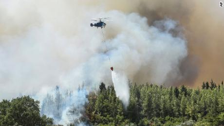 A helicopter fights a forest fire in the village of Kaklarar near the Mediterranean coastal city of Manavgat on Saturday, July 31.