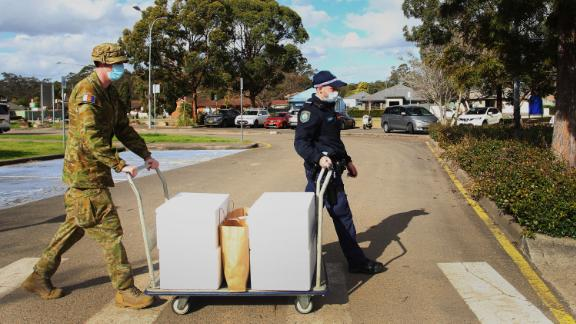 Australian Defence Force personnel and NSW police load food packages for delivery to people in lockdown at the Prairiewood Leisure Centre in Sydney on August 2.