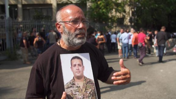 Elias Maalouf stands outside the justice ministry in Beirut holding up a photograph of his son George, who was killed in the blast.