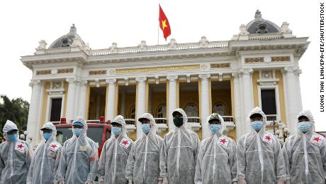 Soldiers from the High Command of Chemicals under Vietnam's Ministry of National Defence before spraying disinfectant throughout the streets of Hanoi on July 26.