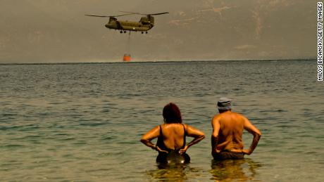 Local residents watch as a Greek army Chinook helicopter collects water as firefighters continue to tackle a wildfire near the Greek village of Lambiri on Sunday.
