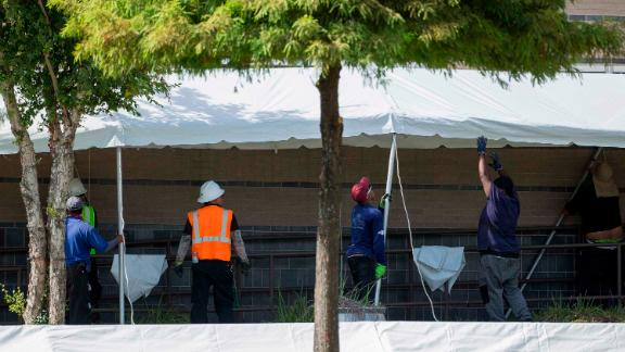 A construction crew works to set up tents that hospital officials plan to use with an overflow of Covid-19 patients outside of Lyndon B. Johnson Hospital, Monday, Aug. 9, 2021, in Houston.