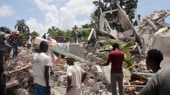 People search through the rubble of what used to be the Manguier Hotel after the earthquake hit on August 14 in Les Cayes, southwest Haiti.