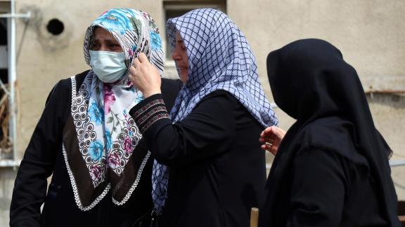 Le donne reagiscono sabato mentre guardano l'edificio distrutto nella città di Bozkurt.