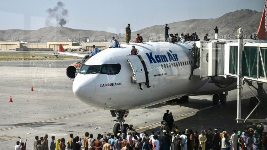 """People climb atop a plane at the airport in Kabul on August 16. Hundreds of people<a href=""""https://www.cnn.com/2021/08/16/middleeast/kabul-afghanistan-withdrawal-taliban-intl/index.html"""" target=""""_blank""""> were on the tarmac, trying to find a way out of the country.</a>"""