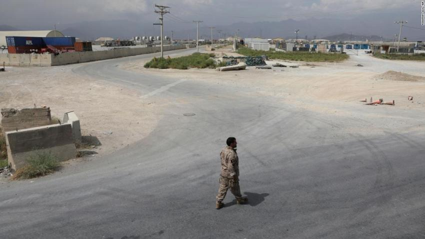 """A member of Afghanistan's security forces walks at Bagram Air Base on July 5 after the last American troops<a href=""""https://www.cnn.com/2021/07/01/politics/us-military-bagram-airfield-afghanistan/index.html"""" target=""""_blank"""">departed the compound.</a>It marked the end of the American presence at a sprawling compound that became the center of military power in Afghanistan."""