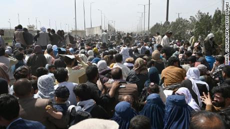 Afghans gather on a roadside near the airport in Kabul on August 20, 2021, hoping to flee from the country after the Taliban's takeover of Afghanistan.