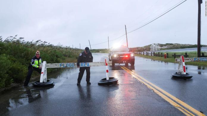 Sgt. Jim Cavanagh and officer Danielle McManus of the Southampton Town Police Department close a flooded road on Long Island, New York, on August 22.