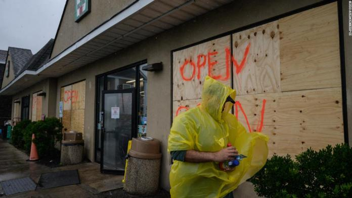 A man walks outside a boarded-up convenience store in Montauk, New York, on August 22.