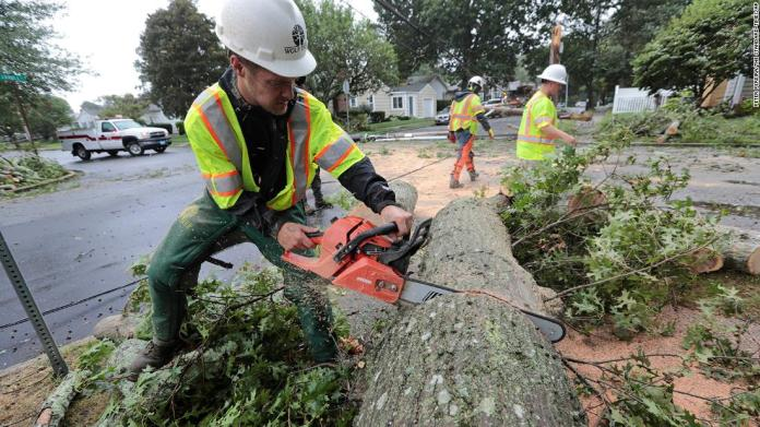 Ryan Bachus, who drove 17 hours from Tennessee with his colleagues to offer assistance, cuts down a tree that fell in New Bedford, Massachusetts.