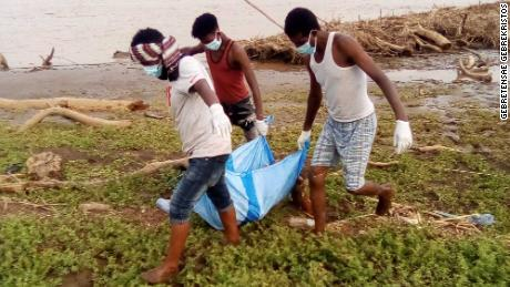 A body retrieved from the Setit riverbank by Wad El Hilou, Sudan, is being carried on plastic wrap.