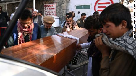 Relatives load in a car the coffin of a victim of the August 26 twin suicide bombs, at a hospital in Kabul on August 27, 2021.