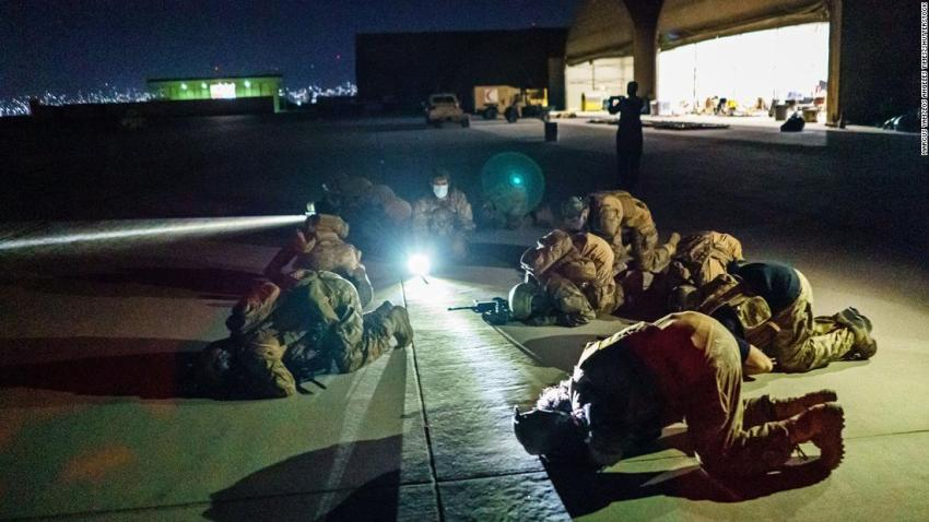 Taliban fighters bow in prayer on August 31 after they secured the Kabul airport and inspected the equipment that was left behind.