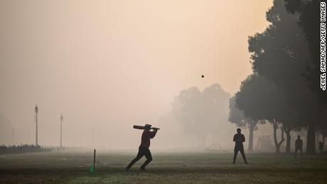 People playing cricket at a park in smoggy conditions in New Delhi on February 8, 2021.