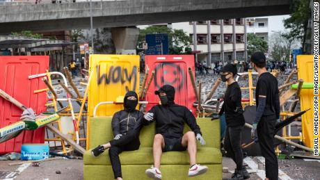 Anti-government protesters sit on a sofa while residents remove barricades built near HKU.