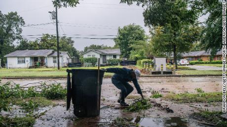 Dallas Baines of Houston threw fallen tree branches in the dustbin.