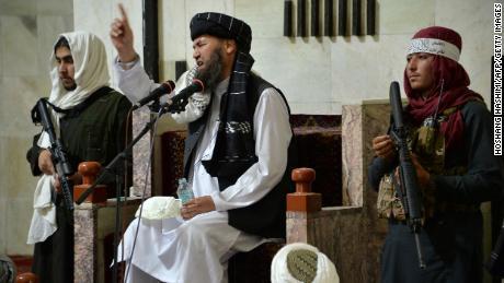 3 सितंबर को काबुल में पुल-ए खिश्ती मस्जिद में जुमे की नमाज के दौरान बोलते हुए एक धार्मिक नेता मुल्ला के बगल में सशस्त्र तालिबान लड़ाके खड़े हैं।